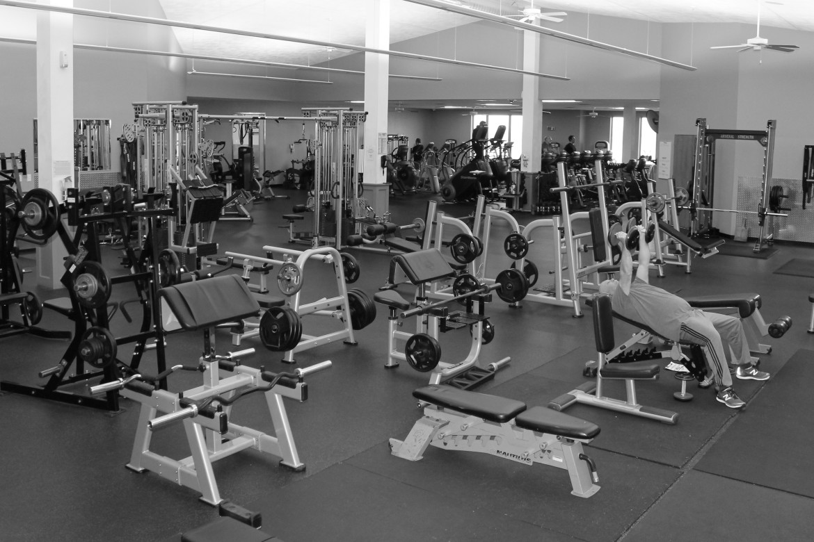 B/W image of gym floor with wide assortment of benches, free weight and other equipment.