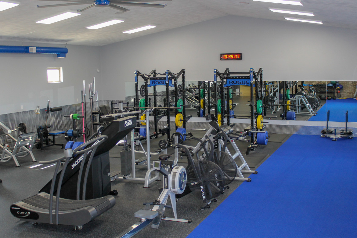 View of gym floor with racks and free weights all over.