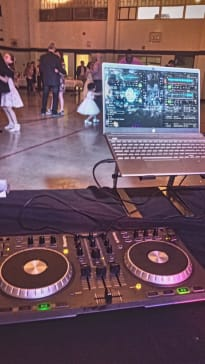 Laptop connected to 2 turntables with older men and young girls dancing in tuxedos and dresses.