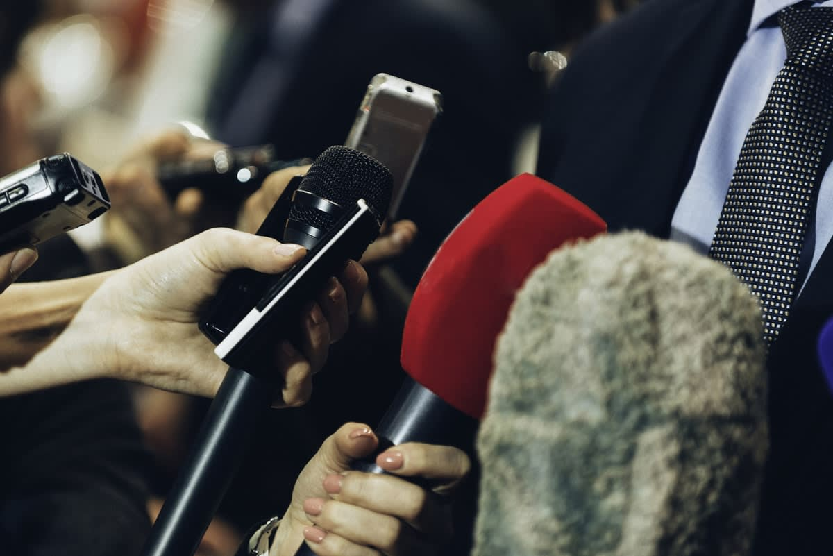 News reporters holding out microphones