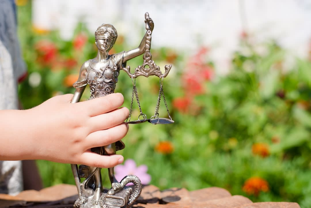 Child's hand holding sculpture of themis, femida or justice goddess on green leaves natural bokeh background