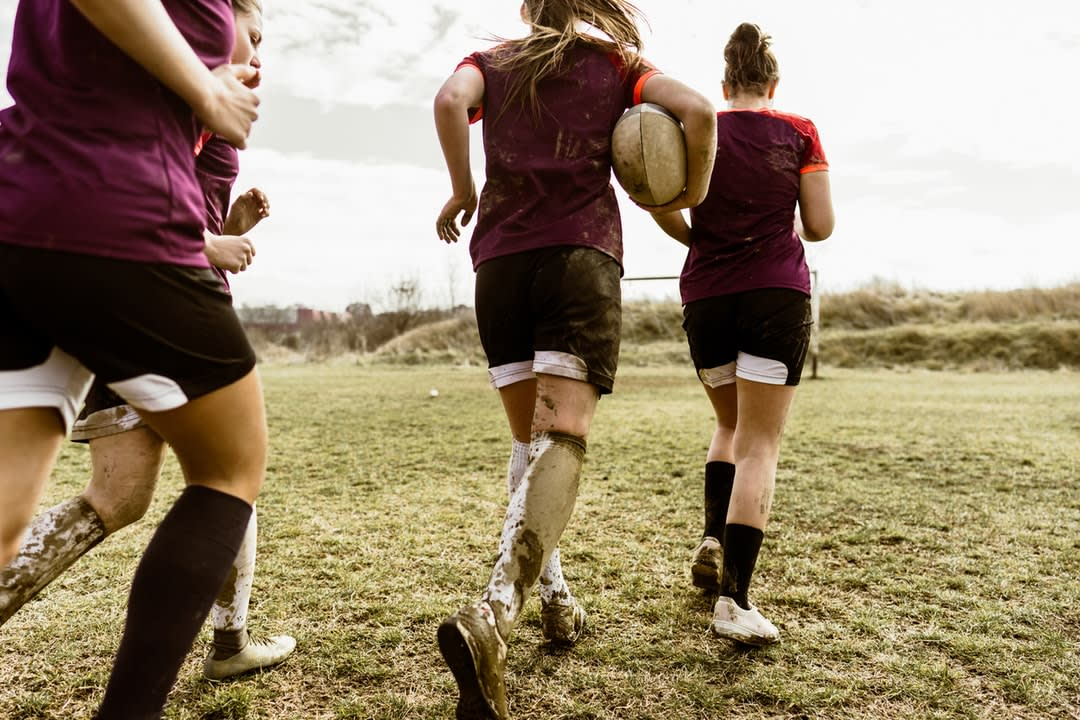 Female rugby players run out onto the ground.