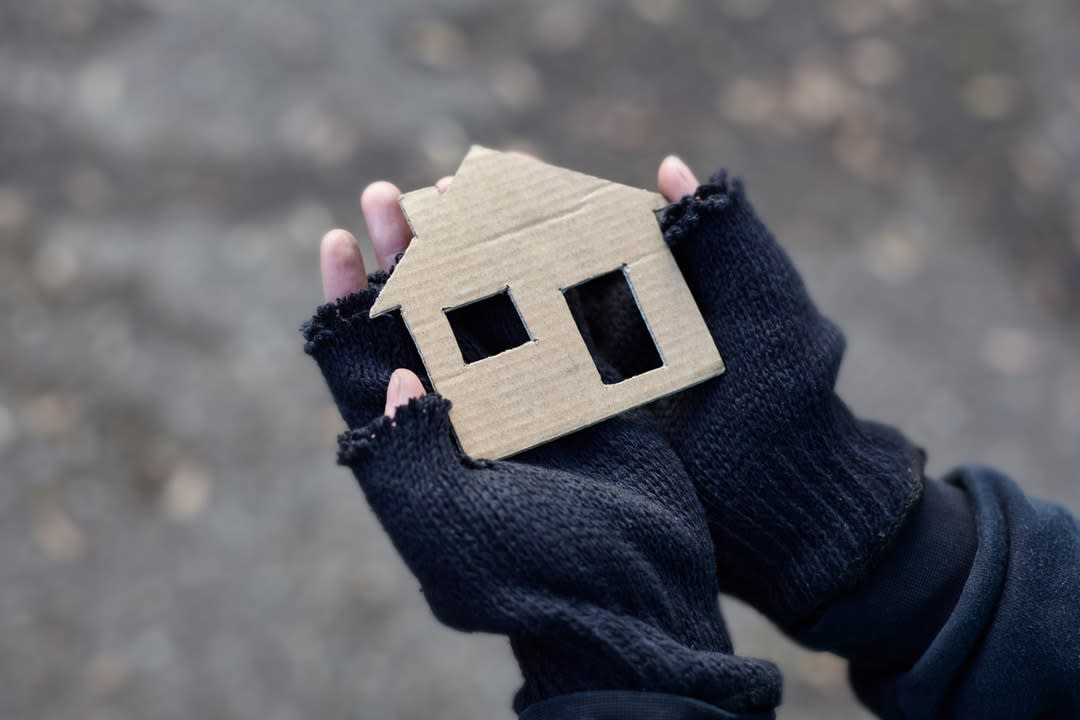 A child's hands in fingerless gloves holds a cardboard cutout of a house.