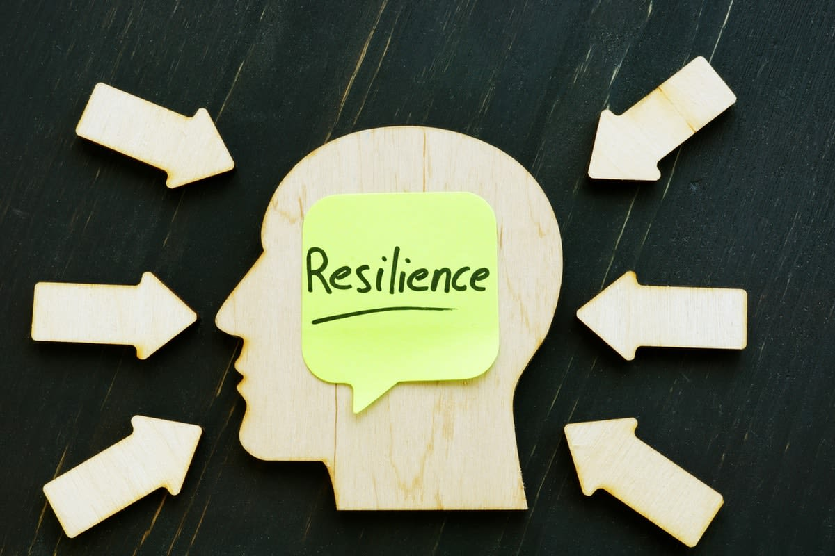 Wooden outline of a head with arrows pointing to it, and the word 'resilience' on a sticky note