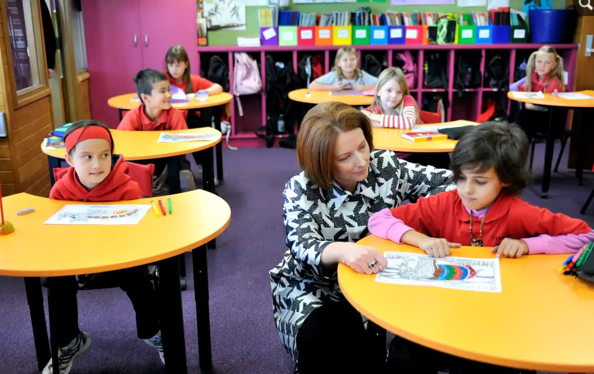 Former prime minister and education minister Julia Gillard in a primary school classroom, crouches down next to a child at a desk