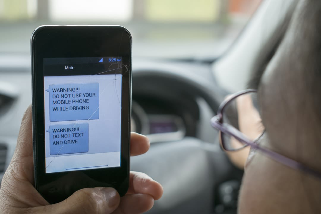 Don't Text And Drive warning on mobile phone held by a motorist.