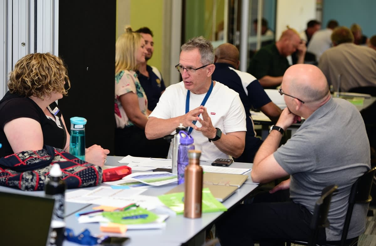 Three Knox School staff in discussion sitting at a table