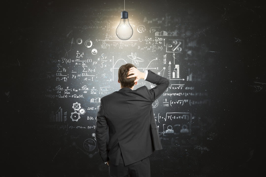 A man stands in front of a blackboard with formulas written in scratching his head and a light bulb illuminating him.