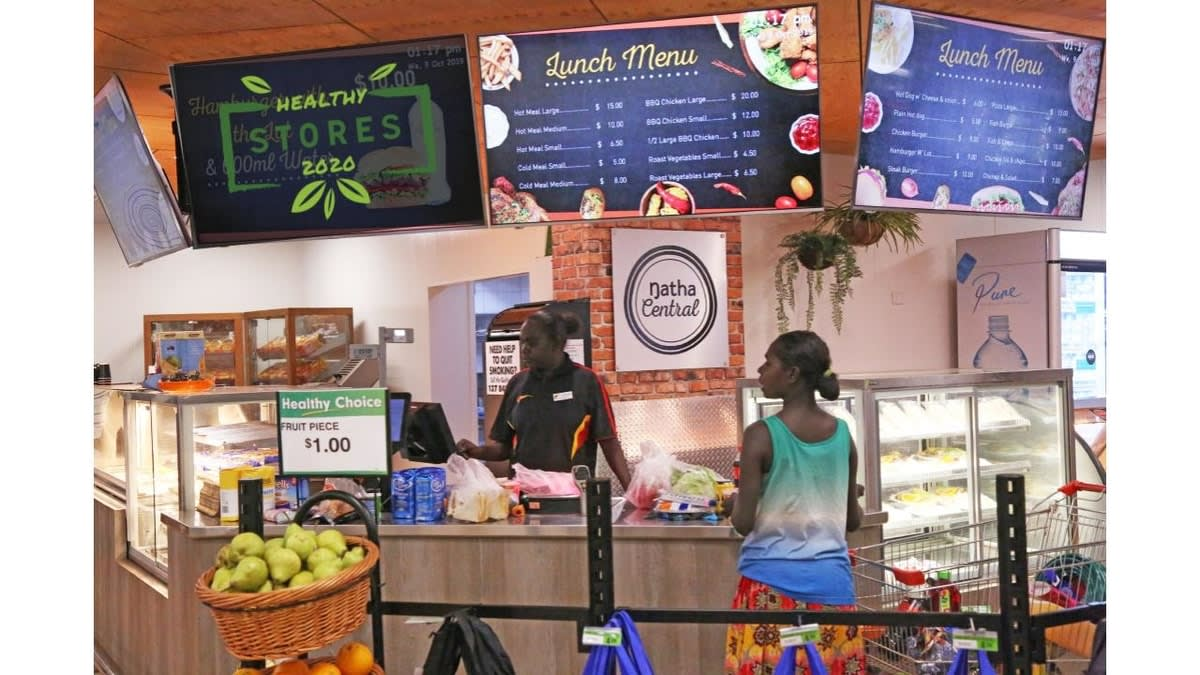 Interior picture of a woman serving a customer in a Healthy Store' in far north Australia