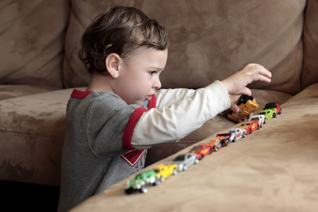 A young child plays with a row of cars on a brown sofa.
