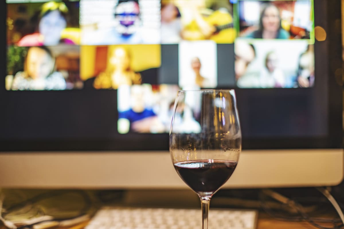 A glass of wine on a table in front of a computer screen.