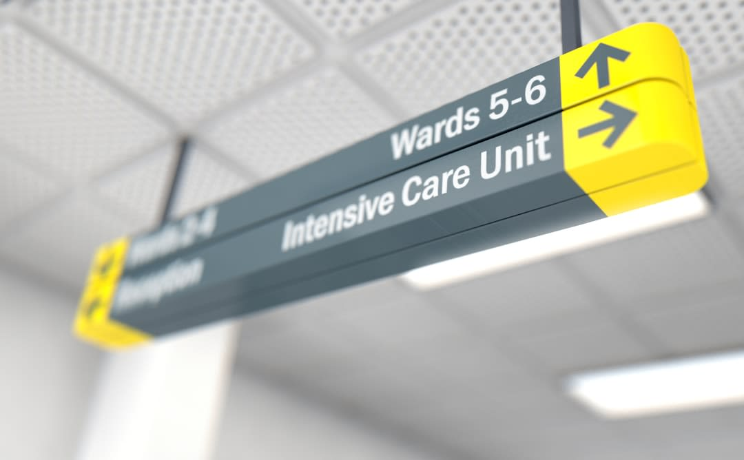 A yellow and grey intensive care ward sign in a hospital.