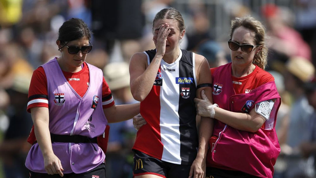 Pic of St Kilda AFLW player being helped from the field by two team medical staff after head injury