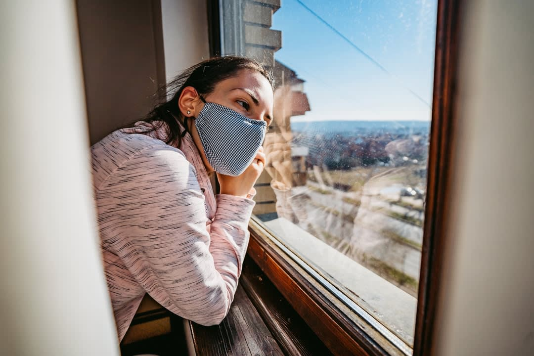 Woman in quarantine looking through the window