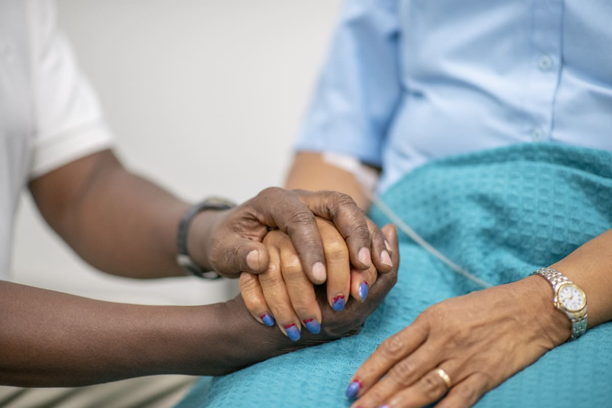 Close-up of care worker's hand, holding the hand of an elderly woman