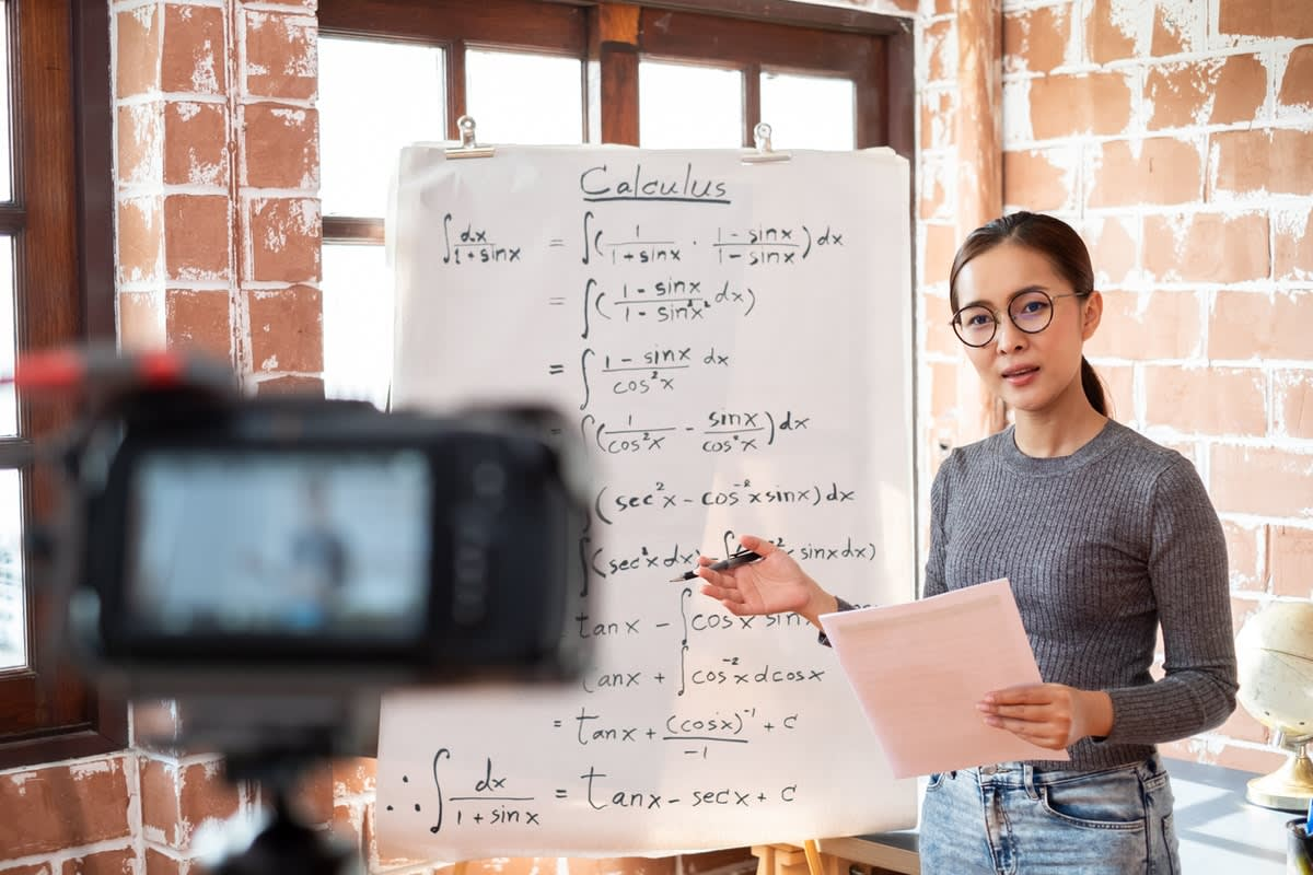 A teacher filming a maths lesson in front of a whiteboard full of equations