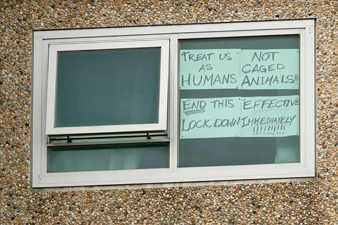 Pic of window in Melbourne public housing tower with signs protesting the COVID lockdown