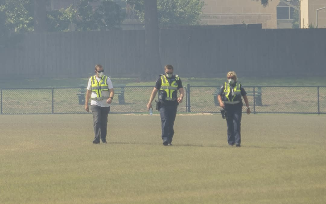 Police wearing protective masks patrol a park.