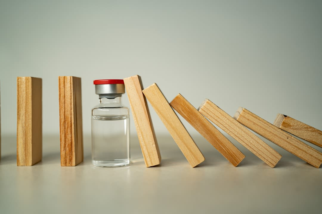 A medicine vial sits between a row of wooden blocks, stopping a domino effect.