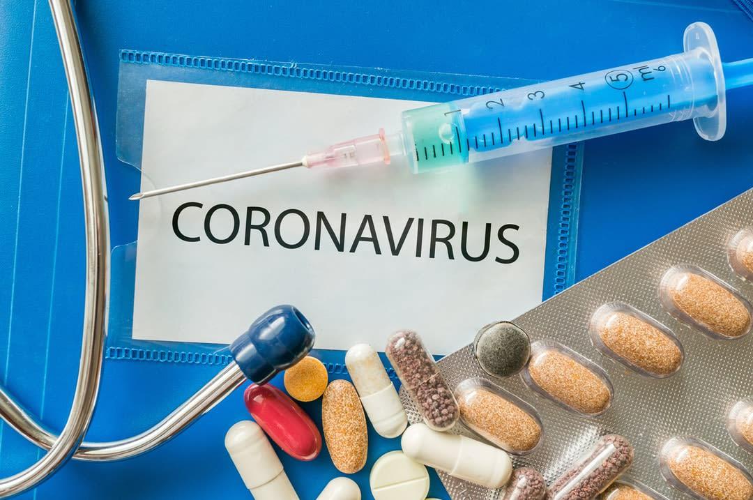 Novel coronavirus disease 2019-nCoV written on blue folder., with pills and a syringe
