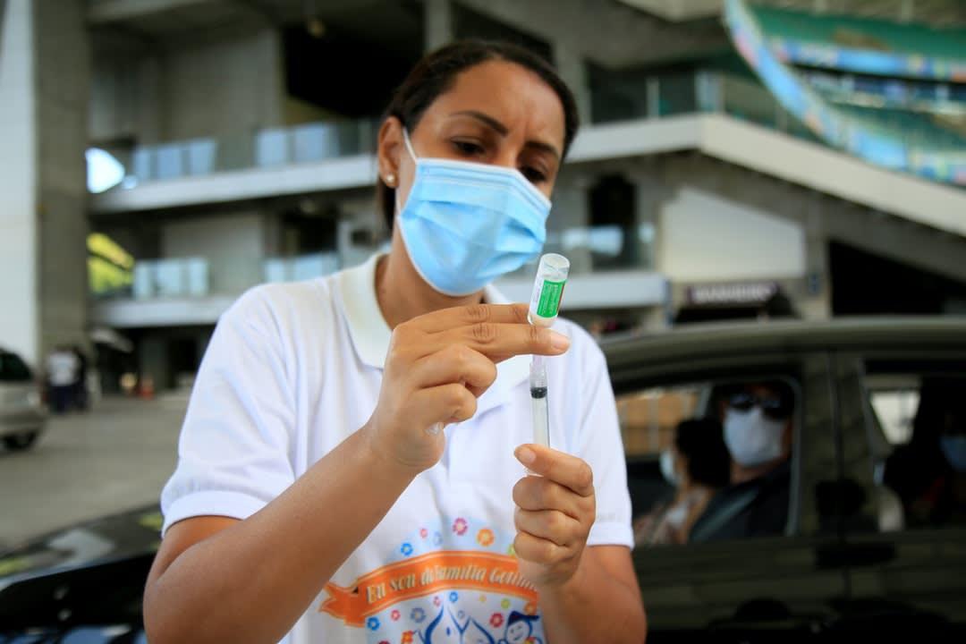 A woman prepares a COVID vaccine.