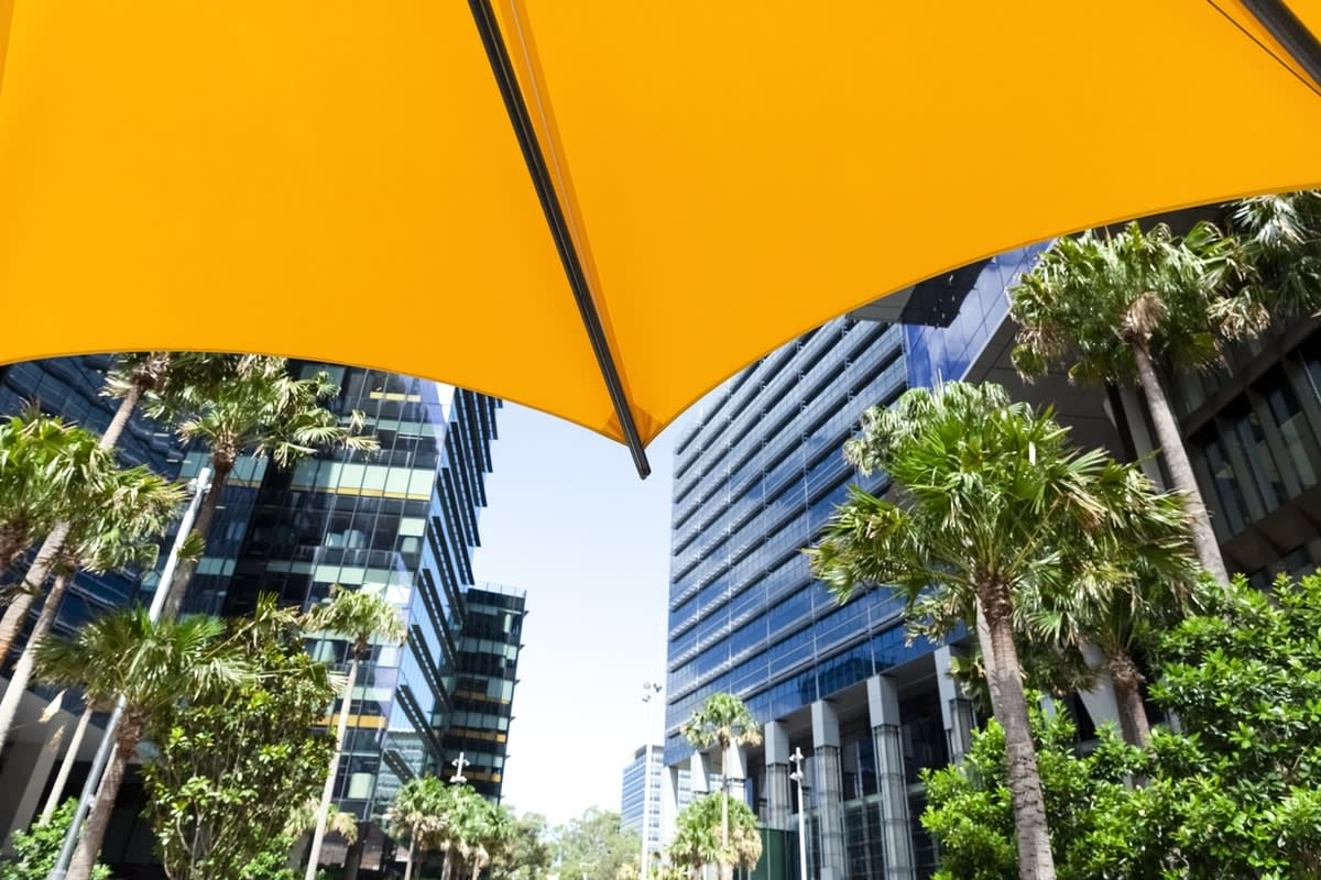 Photo taken from under sun shading of city buildings with surrounding trees