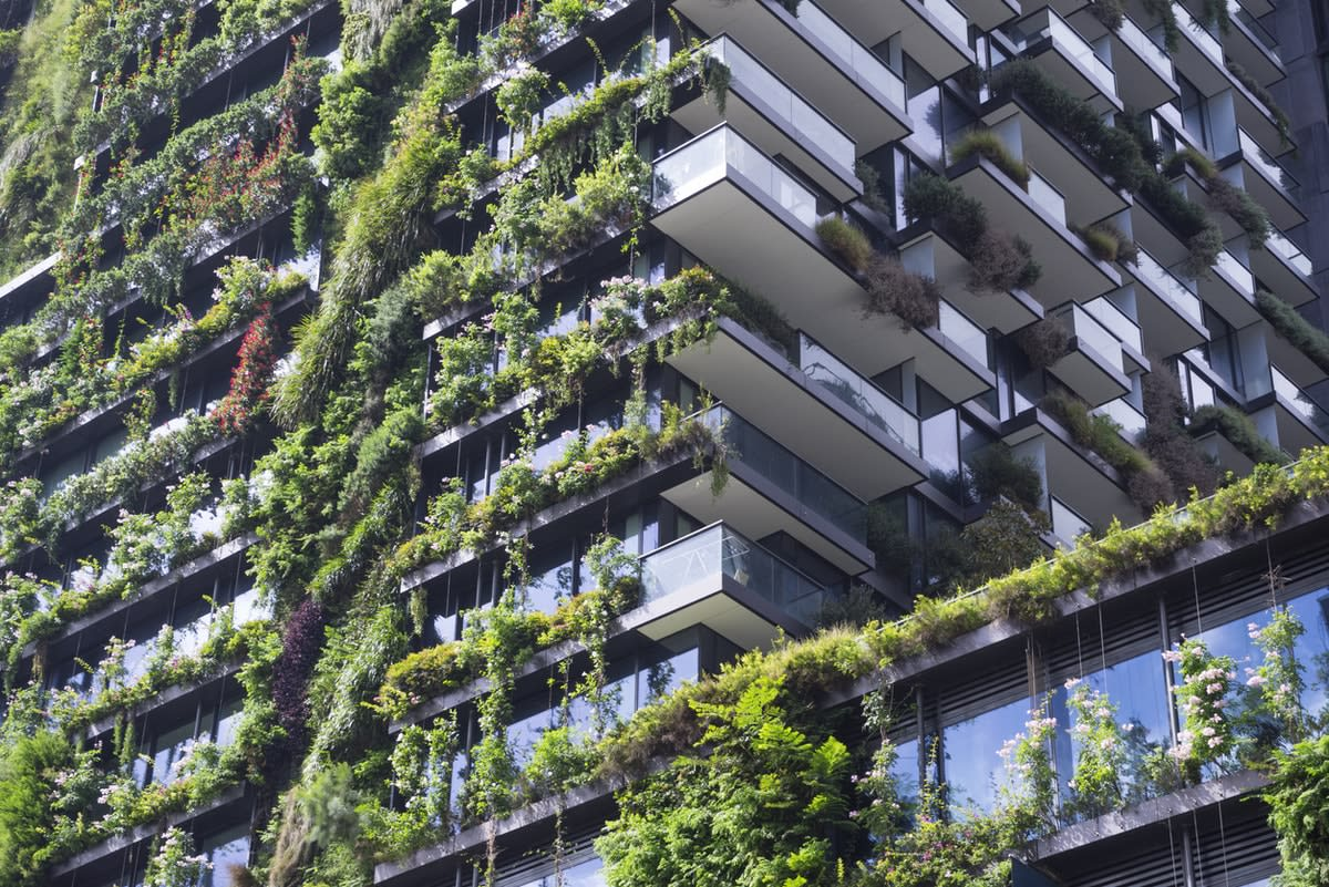 A modern apartment building with hanging vertical gardens on the sides