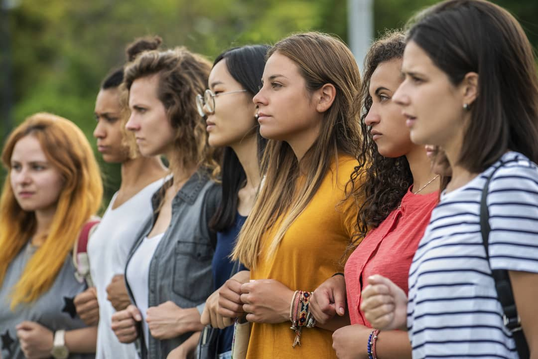 A row of determined women stand in a line locking arms.