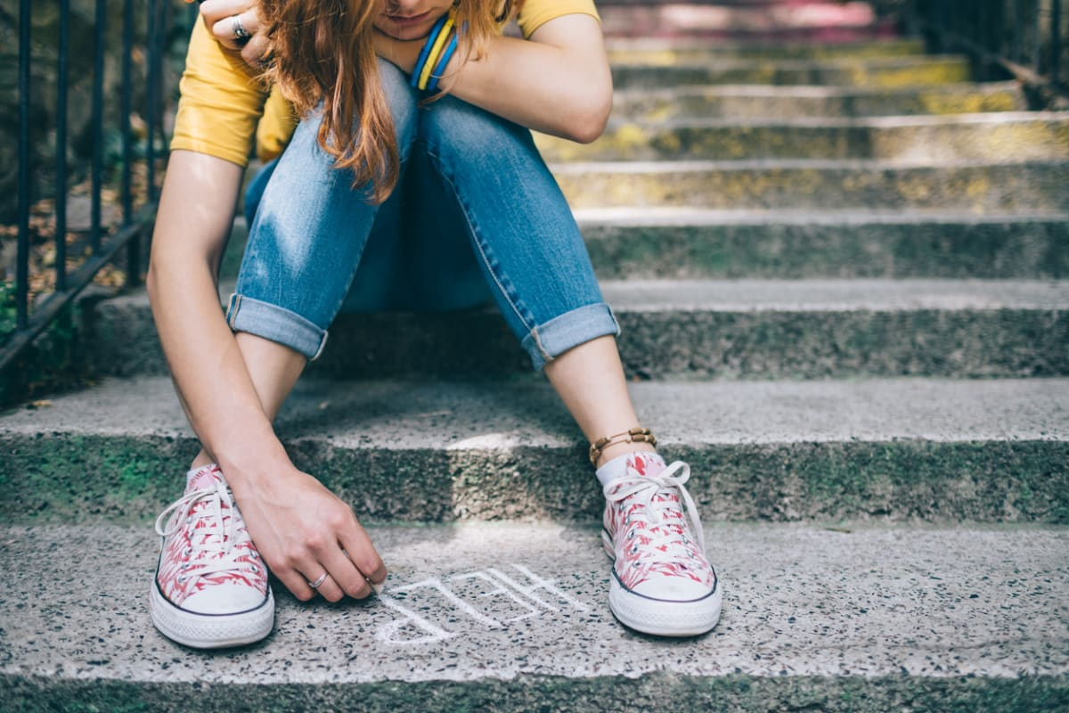 "Girl sitting on steps writing ""Help"" in chalk"