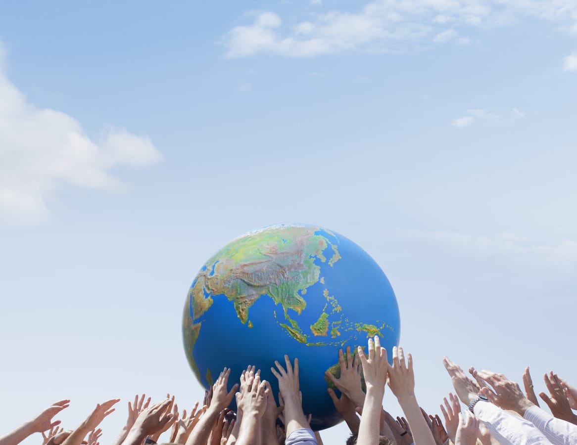 Many holding and reaching for a globe of the world, with a blue-sky backdrop