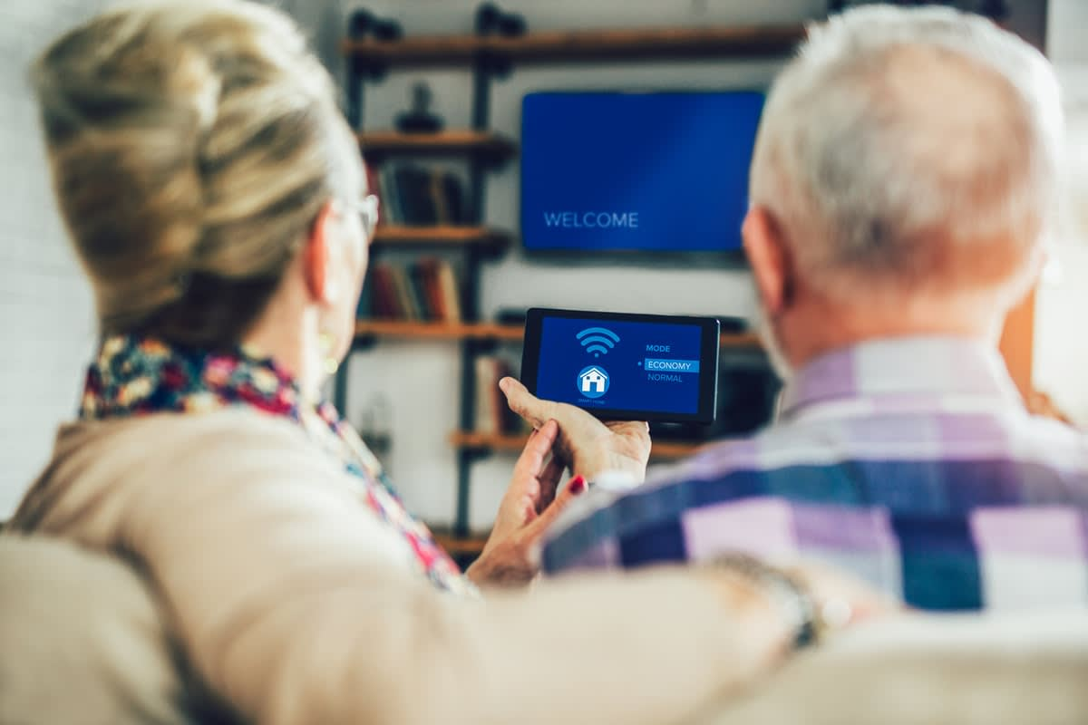 An elderly couple photographed from behind, sitting using a smart-home tablet.