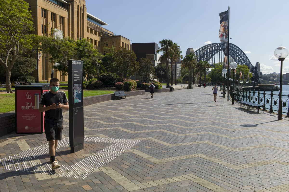 An all-but-deserted Sydney harbour waterfront with the Sydney Harbour Bridge in the background