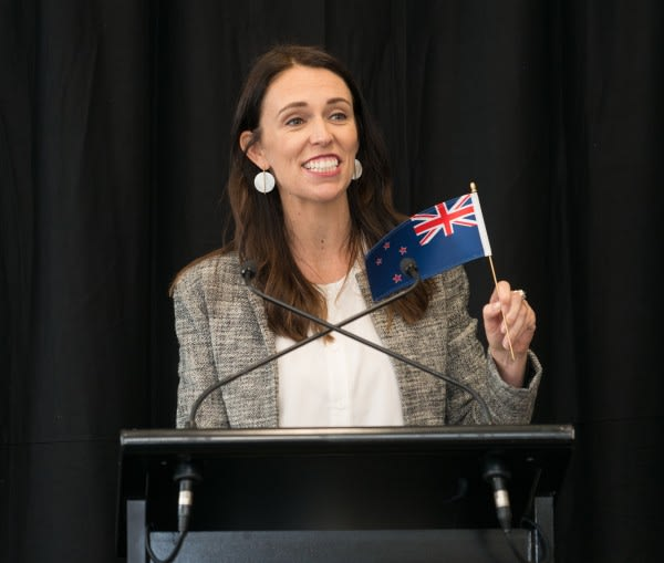 New Zealand Prime Minister Jacinda Ardern at a lectern, holding a small NZ flag.