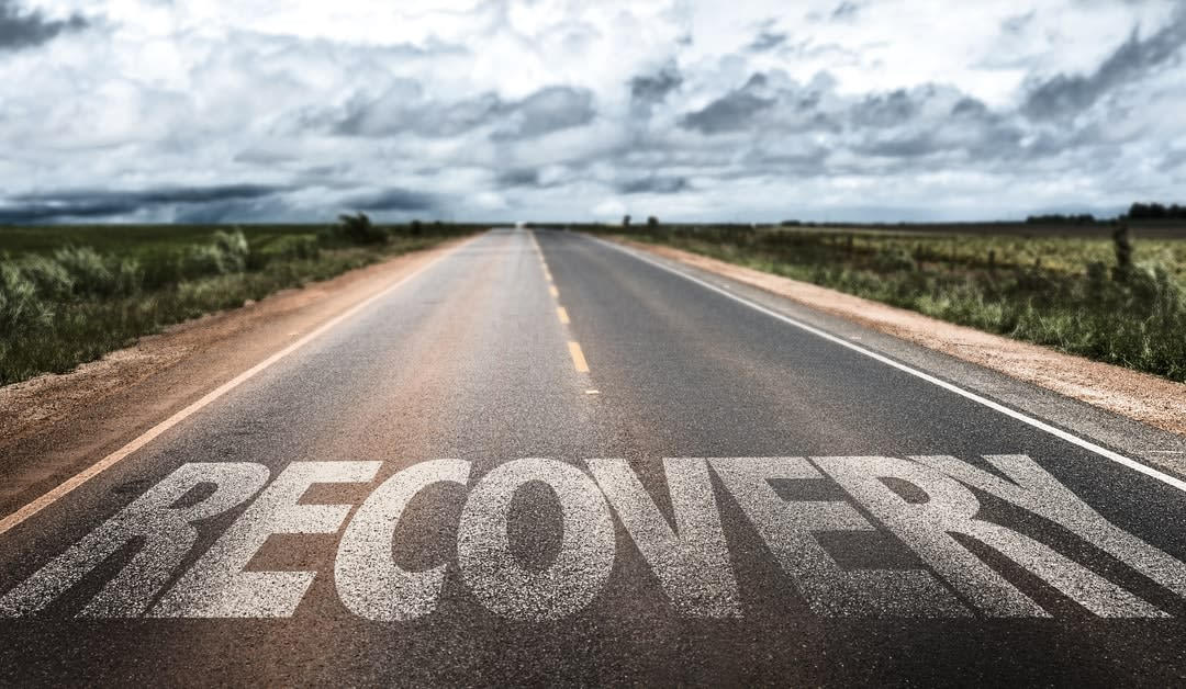 An open road with the word 'recovery' painted on it