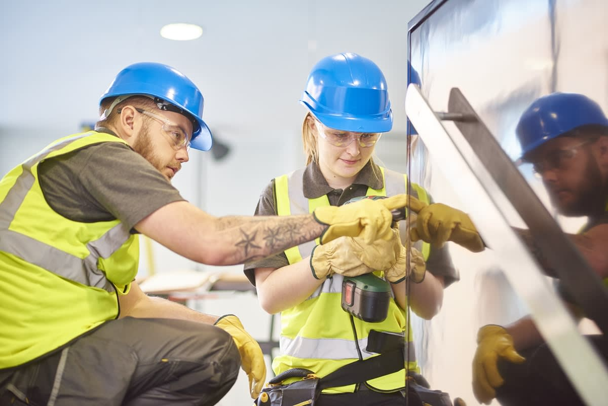 A woman in hard hat and high-vis clothing being instructed by a male dressed the same on using a drill on a construction site.
