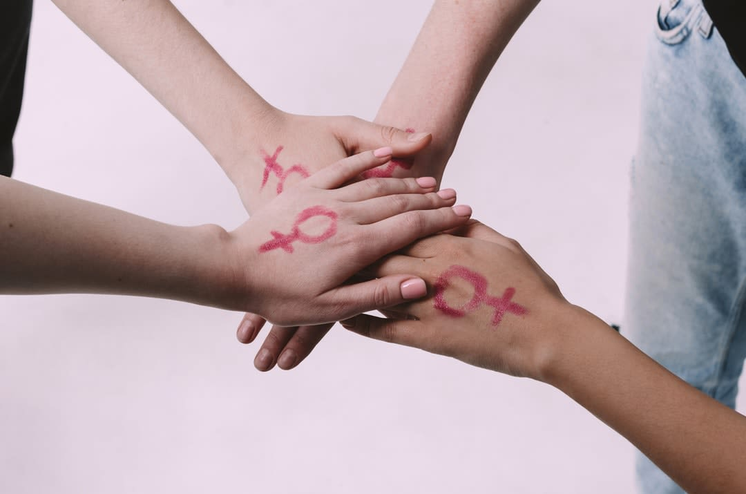 Four women join hands with the femaile gender symbol painted on the back of their hands.