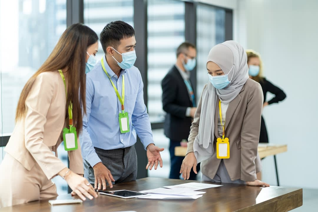 Muslim woman in medical face mask talking with diverse group of colleagues.