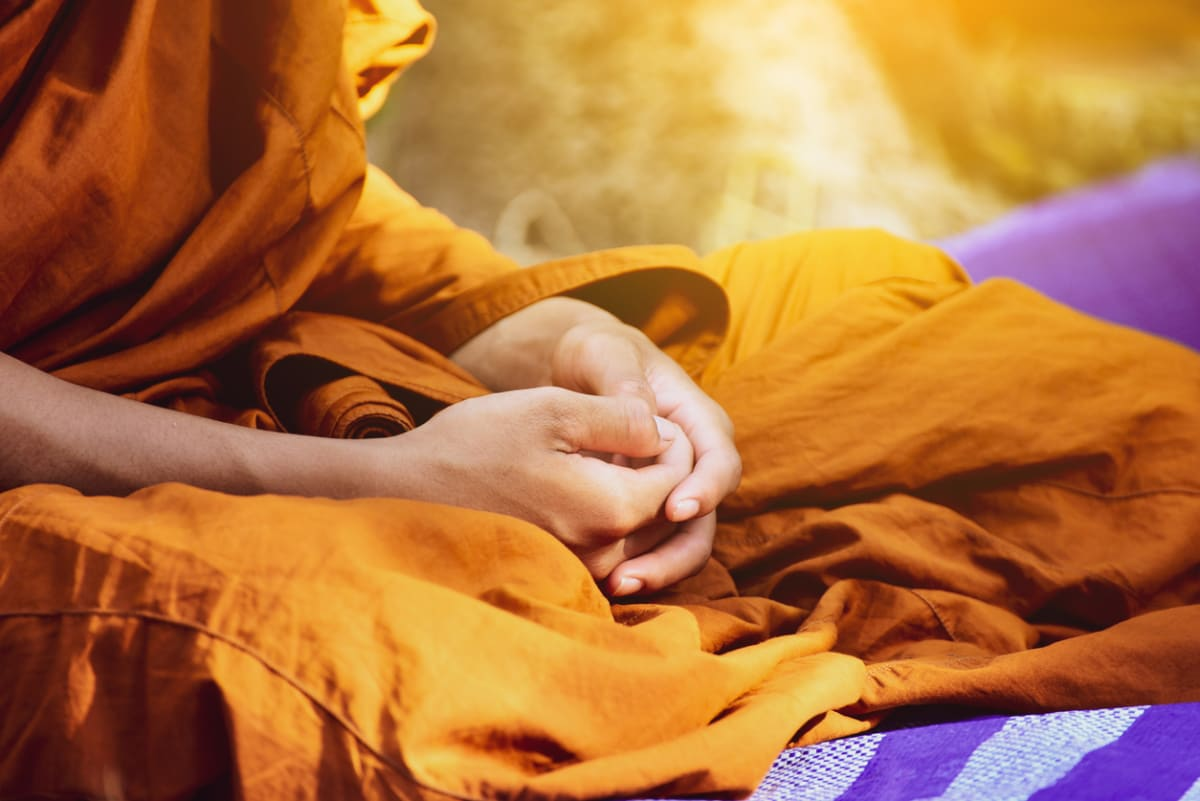 A Buddhist monk's hands clasped in a meditative pose
