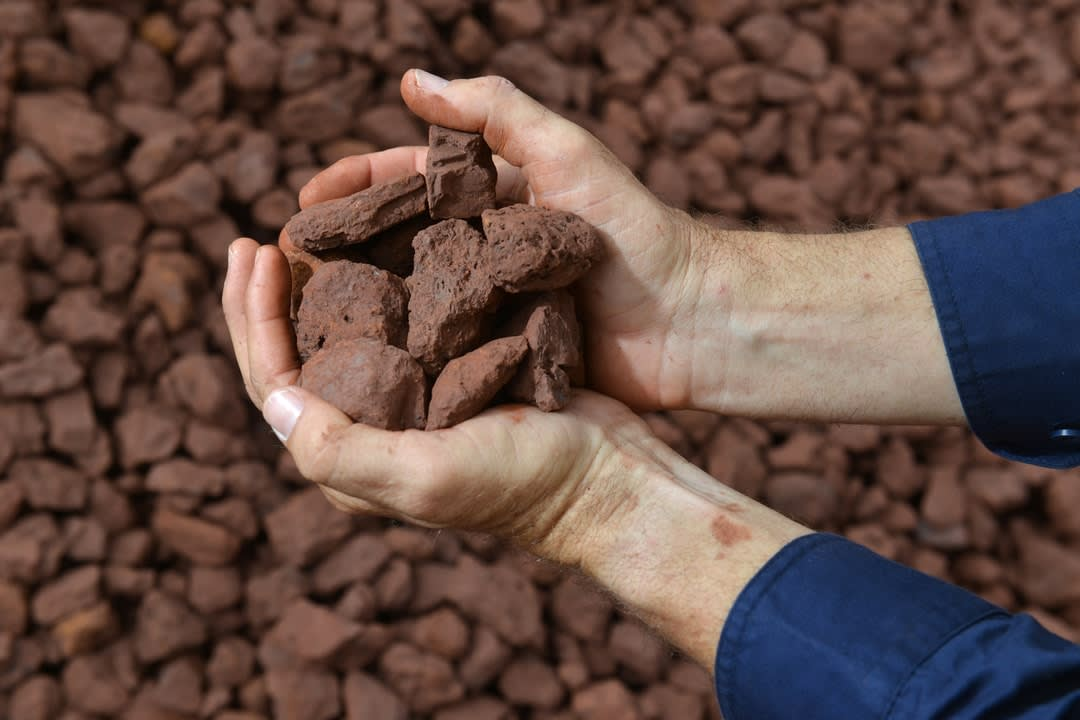 Two hands holding an iron ore sample