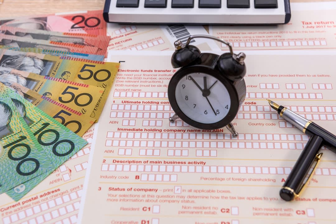 Clock and pen on Australian tax form close up