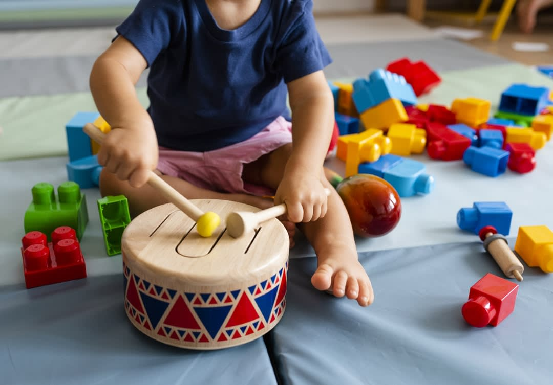 A young child in childcare bangs ion a drum.