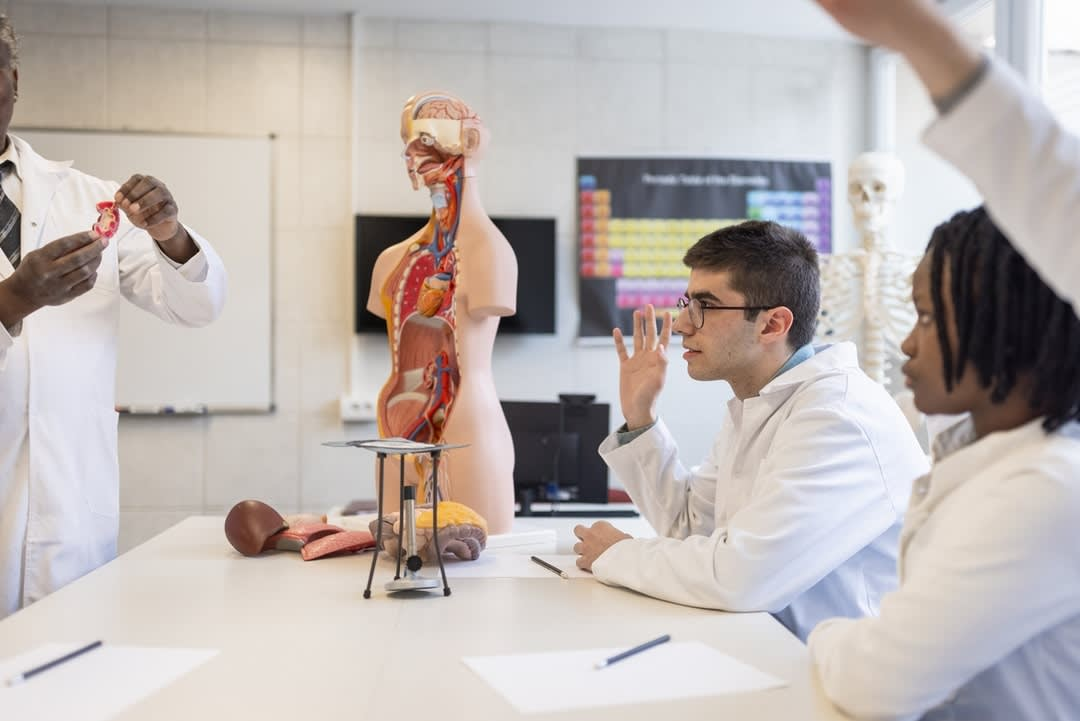 Students in lab coats raise hands to question a lecturer with an anatomical dummy.