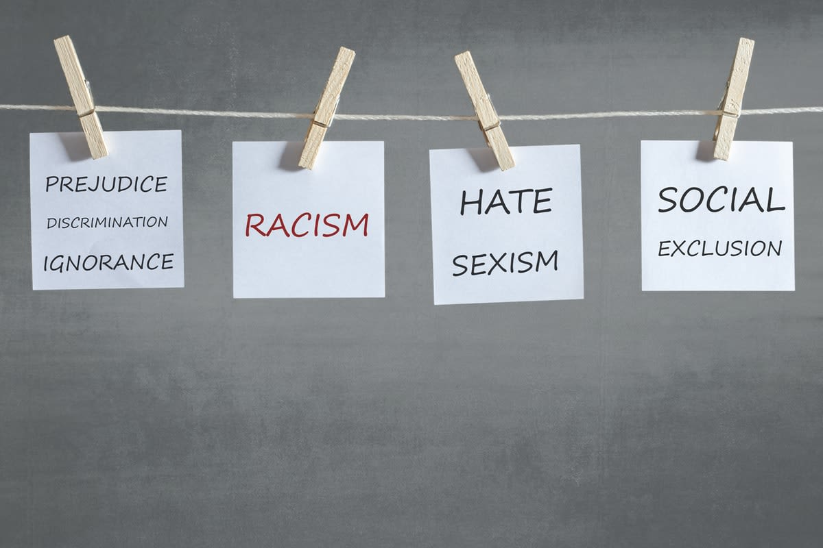Notes pegged to a line, reading 'Prejudice discrimination ignorance'; 'racism'; 'hate sexism'; 'social exclusion'