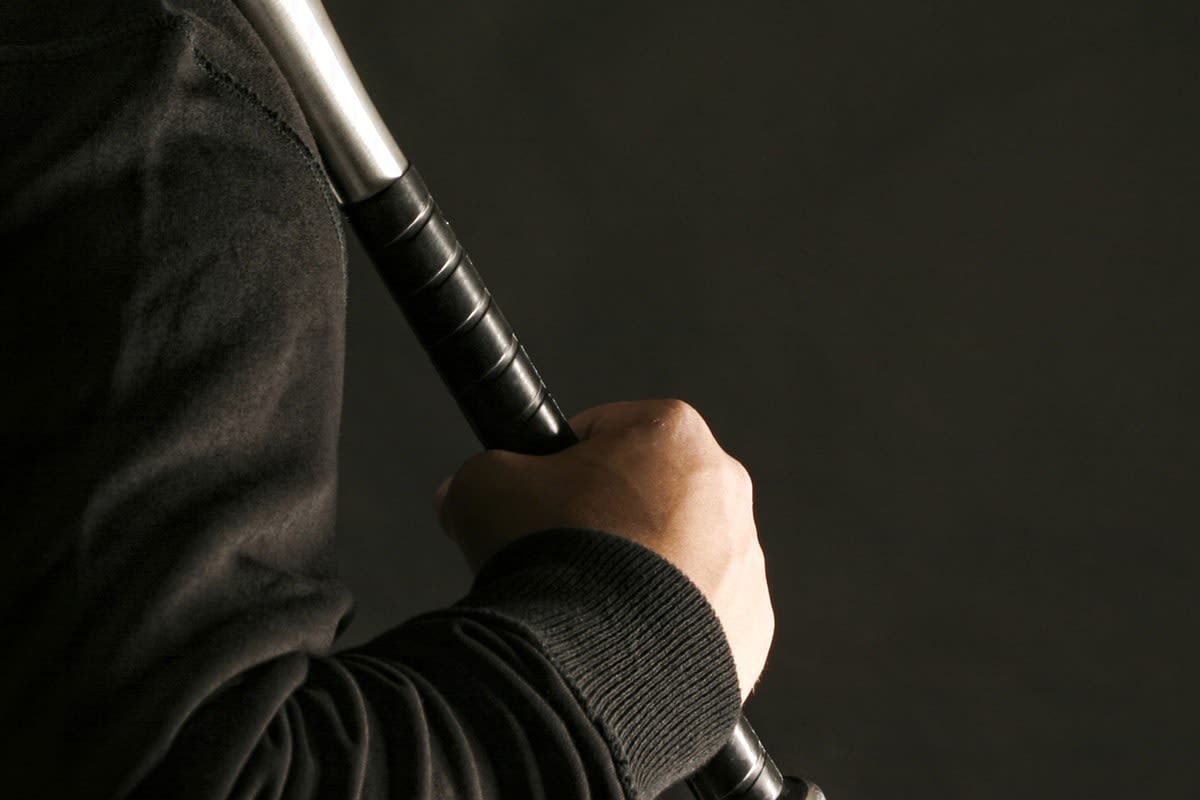 Close-up of a man's hand holding a baseball bat in a threatening manner