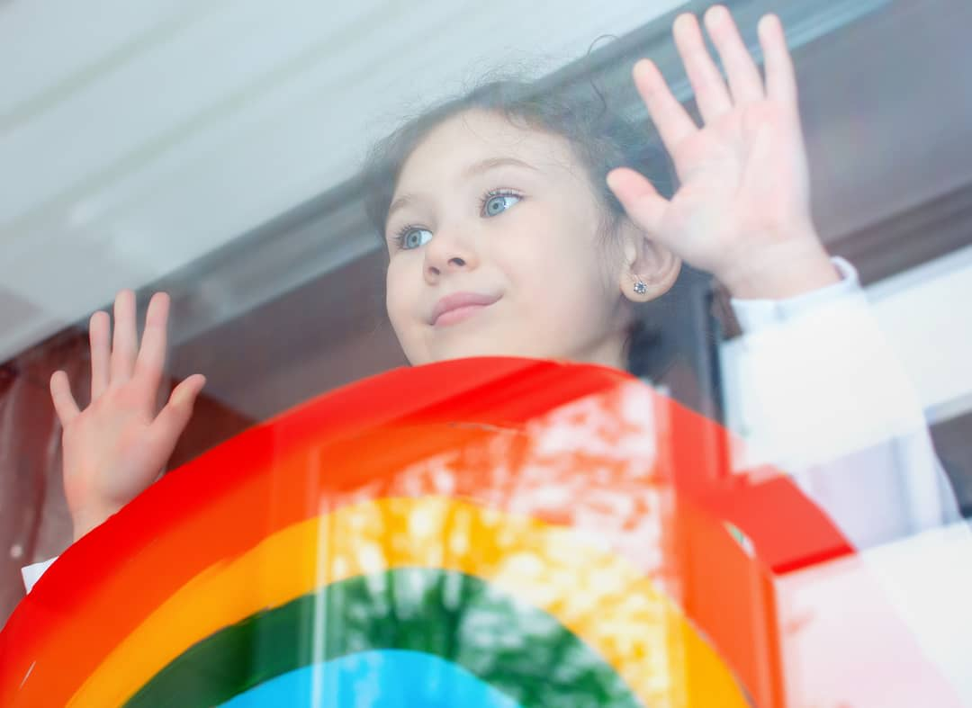 Little girl with hope looks out the window on which a rainbow is painted