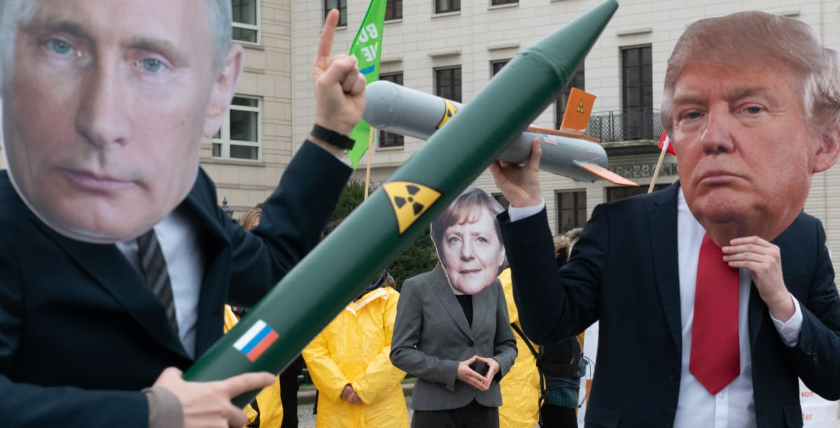 Demonstrators with a Putin and Trump mask and a Merkel mask face each other with rocket models on Pariser Platz. They are protesting with their action against the imminent end of the INF disarmament agreement between Russia and the USA.