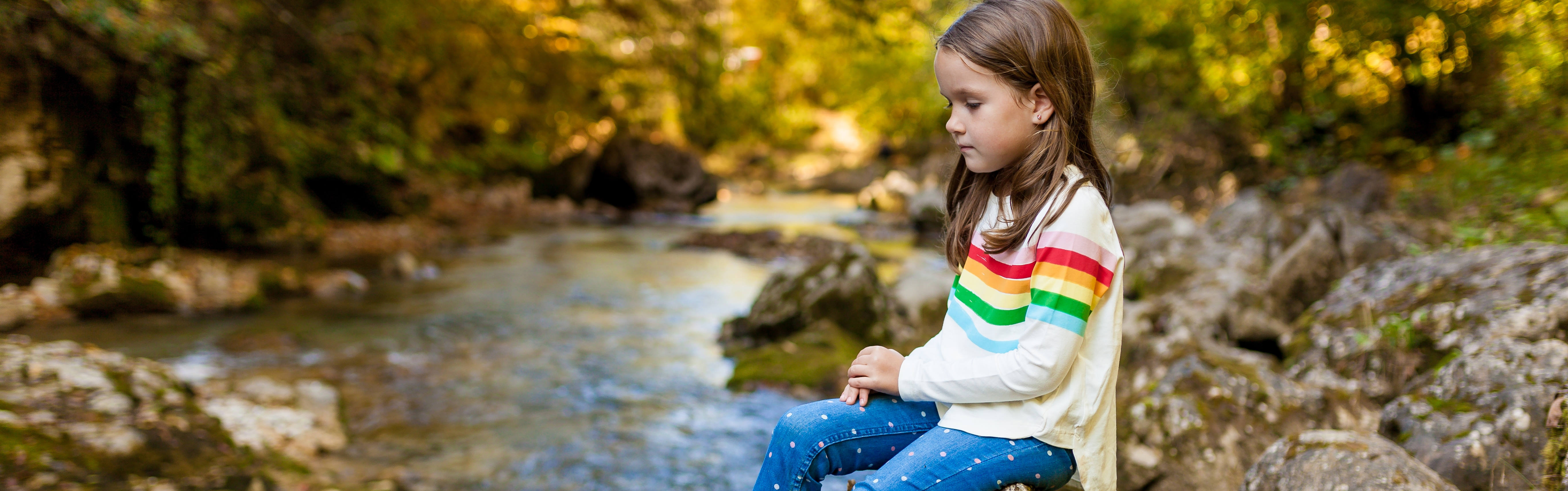 Girl by Stream in Fall