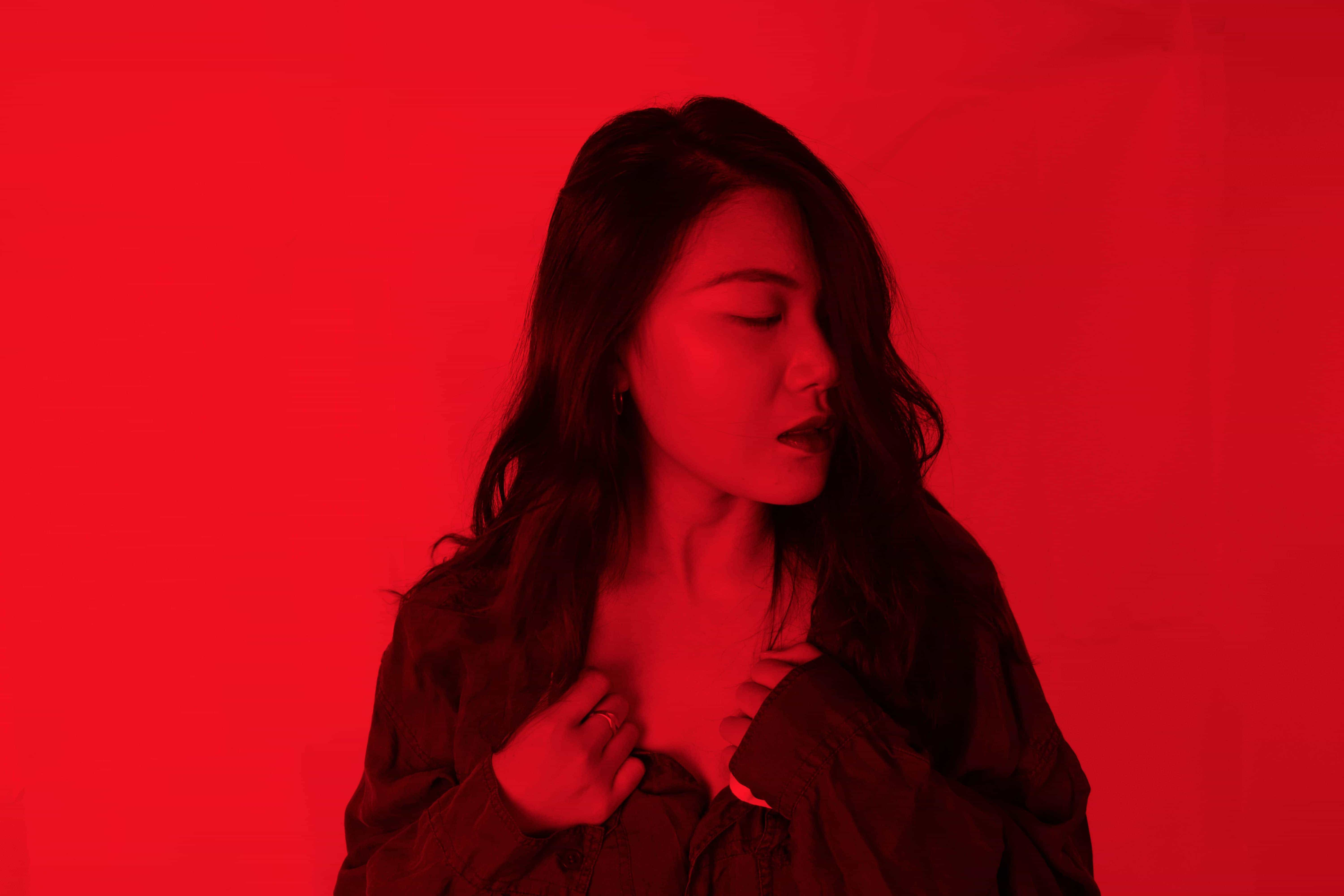 A woman clutching at the neck line of her shirt with eyes closed in contemplation with the photo having a red overlay.