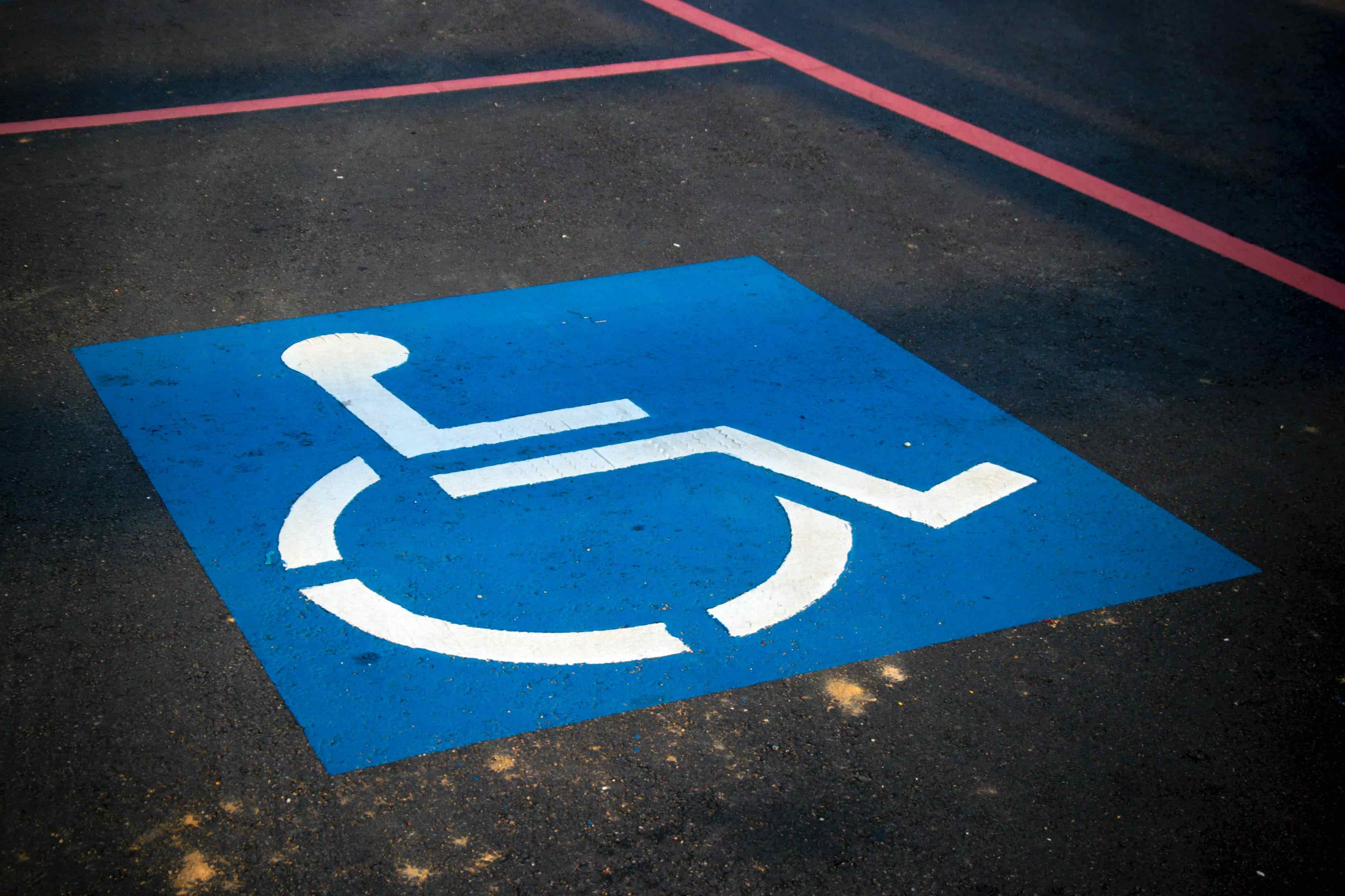 The symbol for a handicapped parking space with the blue square and white figure sitting in a wheelchair.