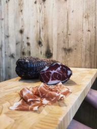 """Capocollo marinated in wine: Nero di Troia, typical of Gargano - Capocollo is similar to what is known as """"Coppa"""" and is found in Corsica and Northern Italy.  Our capocollo is carved from the loin of the pig and marinated in Nero Di Troia wine, a typical Apulian grape variety. It is carefully flavoured with our own aromatic herbs during the salting process, giving it a sweet Gargano aroma.   It is then carefully tied during the drying process to give it all its characteristic mellowness. It reveals all its flavours and generosity cut into thin slices: its flesh is tasty and its fat very fine, its chewiness is pleasant in the mouth.  It can be eaten in foccacias, in sandwiches, flavoured with a little Olio di Serra extra virgin olive oil, as an aperitif with cheese... Many combinations are possible, but it is surely tasted alone that it reveals all its splendour. It is a real discovery.  Capocollo marinated in Nero di Troia is gluten-free. It is offered in pieces of approximately 1.5 kg, vacuum packed with a shelf life of 6 months."""